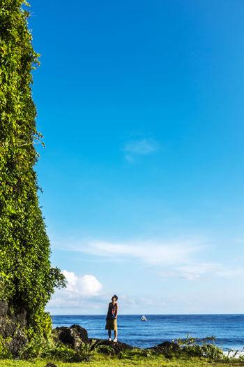 Man looking up at overgrown rock at seaside