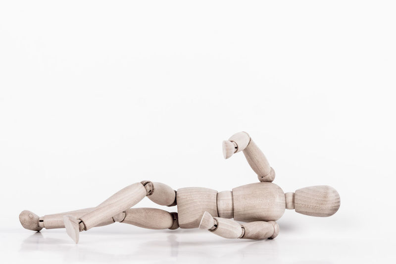 A wooden puppet is laying at ground as for an accident happend First Aid SUPPORT Skeleton Accident Assistance Concept Crack Cure Danger Dummy Fall Fallen Help Human Lay Medical Metaphor One Person Puppet Safety Studio Shot Weak White Background Wounded