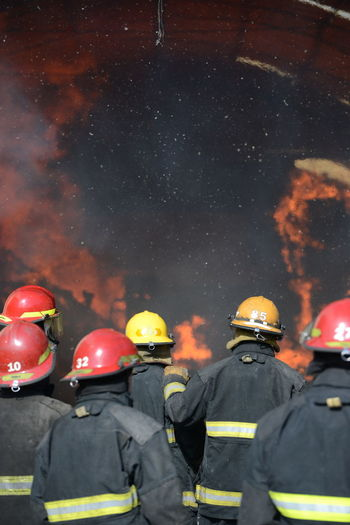 Rear view of firefighters standing against fire