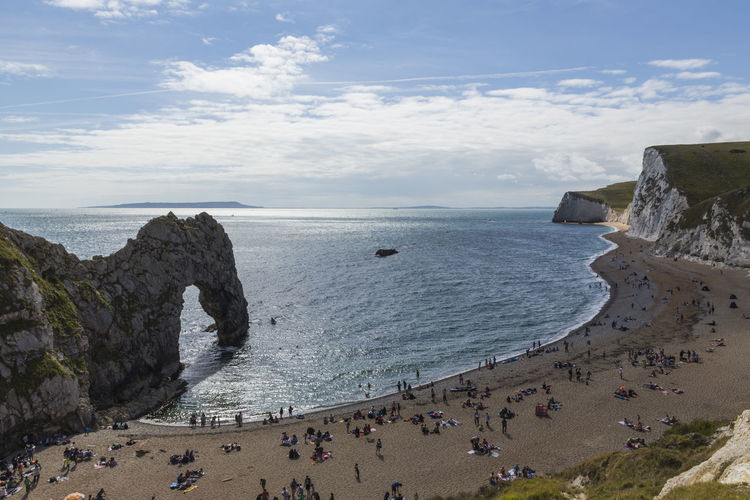 Durdle Door and Bat's Head, Purbeck District, Dorset, England, United Kingdom Beach Beauty In Nature Cliff Day Horizon Over Water Large Group Of People Men Nature Outdoors People Real People Sand Scenics Sea Sky Tranquility Water Women