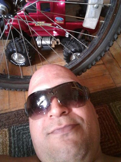 TRUCKS RUGS & rims/sun & shades #EGGHEADEGGLAND Looking At The Camera BETWEEN THOUGHT AND EXPRESSION #LOVEDDYJRPLATONICNIEVES L TRUCKS RUGS And Rims/sun& SHADES Men Portrait Smiling Headshot Close-up One Mature Man Only Sunglasses Shaved Head