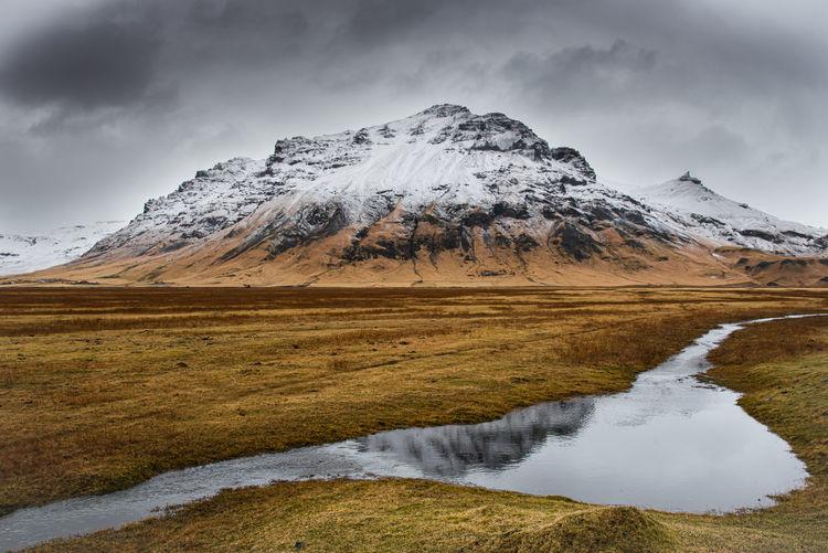 Snowcapped katla volcano mountain on icelandic medow reflected on water in iceland