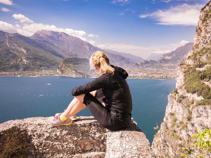 Woman sitting on rock looking at mountains against sky