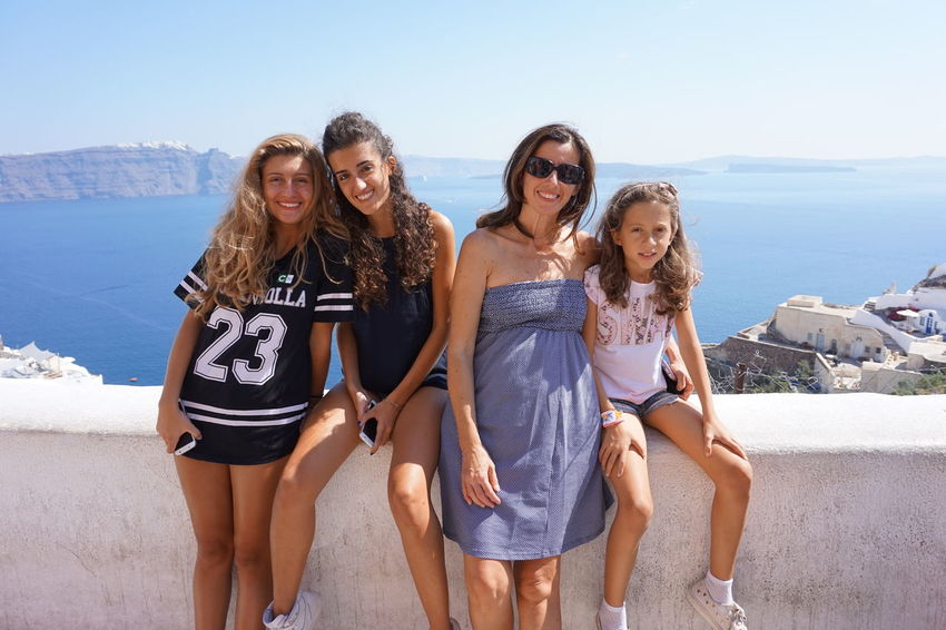 Girls in Santorini Connected By Travel Beach Bonding Cheerful Day Enjoyment Friendship Front View Fun Happiness Leisure Activity Long Hair Looking At Camera Nature Outdoors Portrait Real People Sea Sky Smiling Standing Sunlight Togetherness Vacations Young Adult Young Women