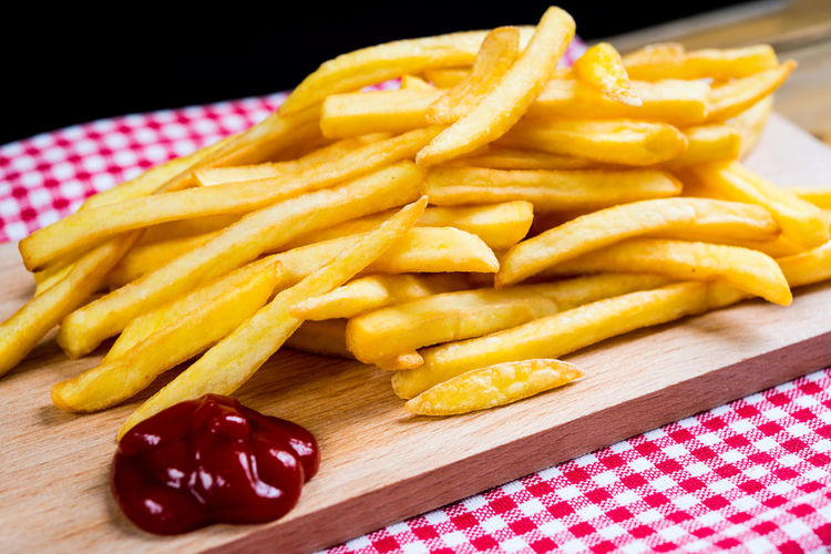 French fries with ketchup on cutting board against black background