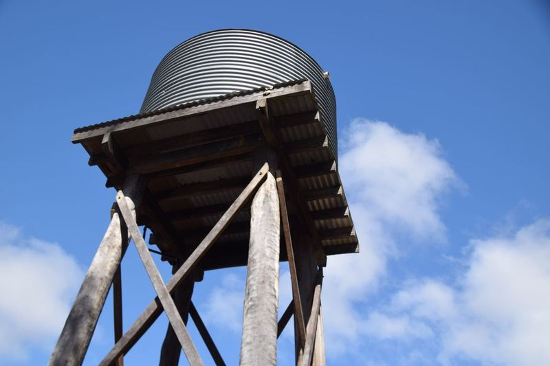 Low angle view of water tower against cloudy sky on sunny day