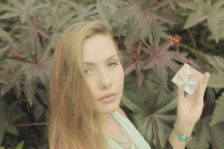 Portrait of young woman holding prism while standing against plant