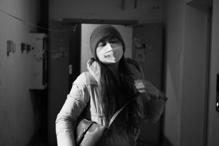 Portrait of beautiful young woman standing in corridor