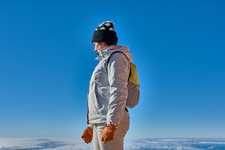 Side view of woman standing against clear blue sky during winter