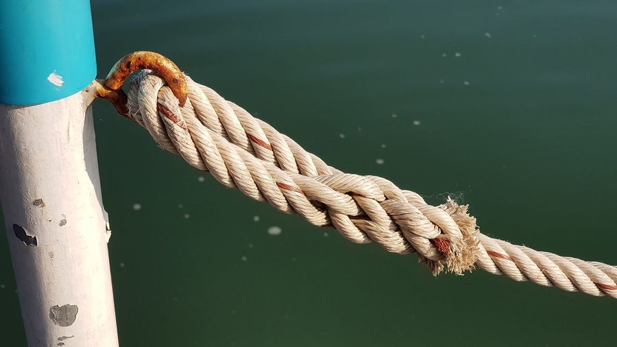 High angle view of rope tied up to pole against sea