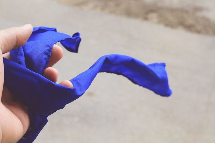 Cropped hand of person holding blue textile on road
