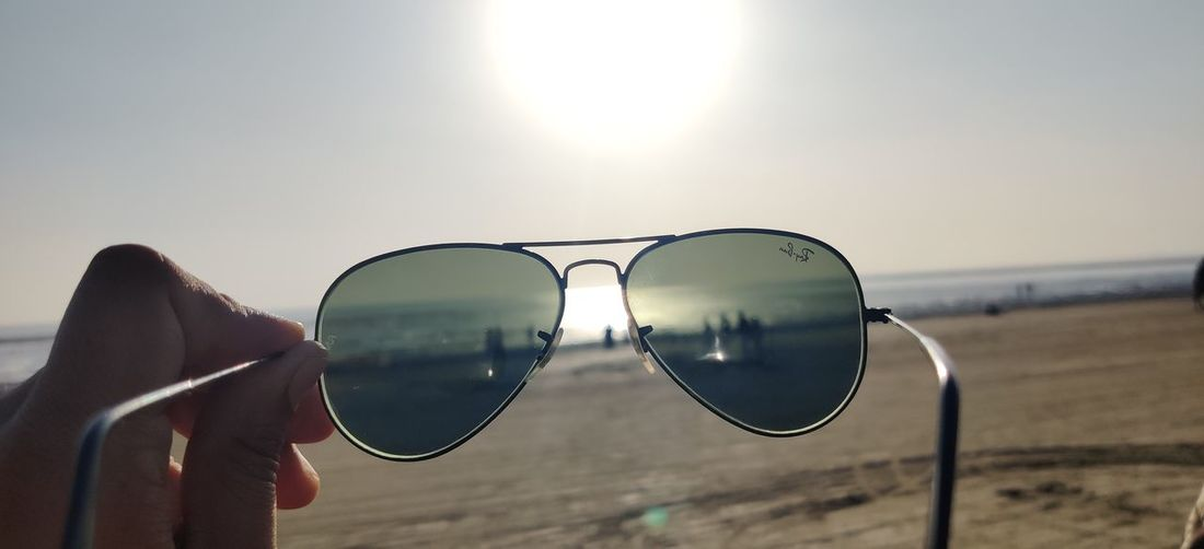 Cropped image of person holding sunglasses against sky