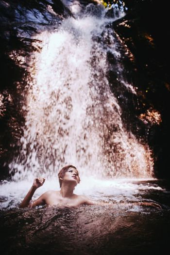 Shirtless Woman Swimming In River Against Waterfall