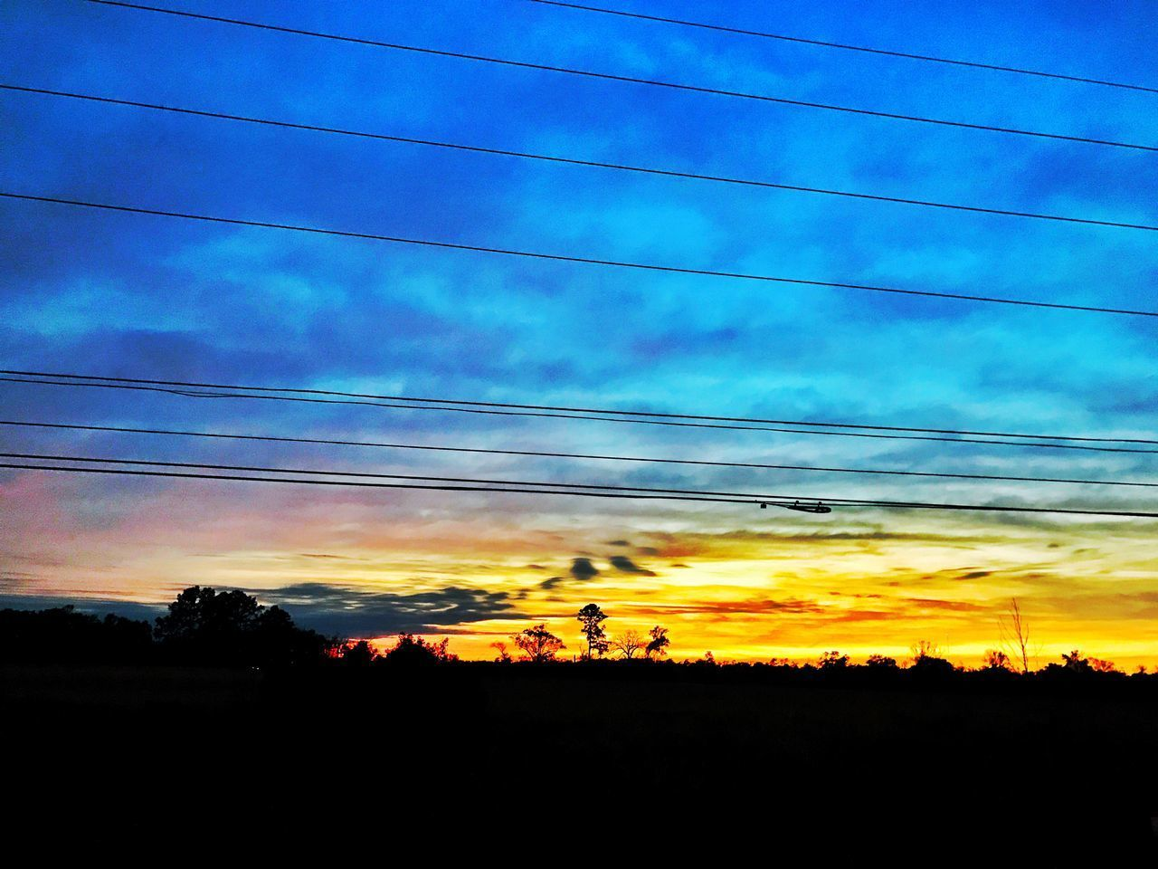 silhouette, sunset, sky, nature, cloud - sky, beauty in nature, scenics, cable, tranquil scene, outdoors, field, tree, tranquility, landscape, low angle view, no people, blue, technology, electricity pylon, telephone line, day