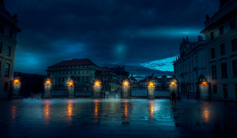 Illuminated buildings by wet street against sky at night