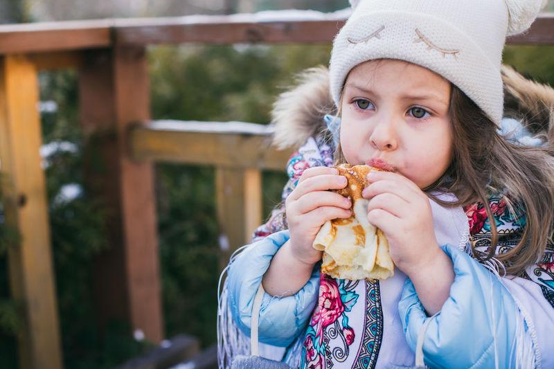Cute girl eating food outdoors