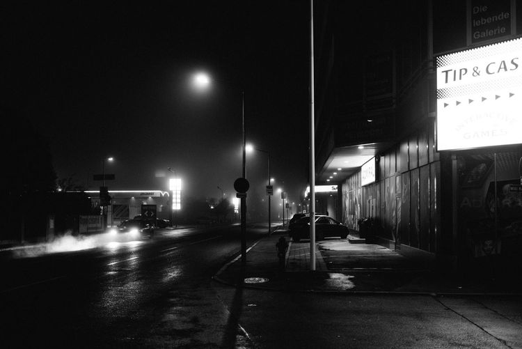 stay out or miss out. Night Illuminated Built Structure Transportation Architecture Building Exterior Outdoors Street Light Real People City Fog Nightphotography Streetphotography Shootermag EyeEmBestPics EyeEm Gallery EyeEm Best Shots Black And White Friday