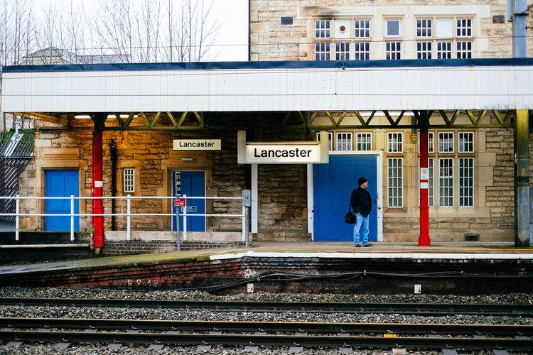 A man wait for a train in at Lancaster Train Station Lancashire Lancaster Waiting Waiting In Line Architecture Building Exterior Built Structure One Person Rail Transportation Railroad Track Real People Rural Scene Train Station