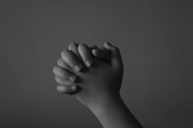 Cropped hands of child praying against gray background