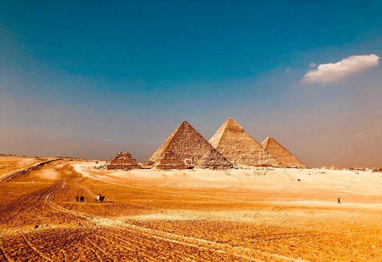 Pyramids at desert against blue sky
