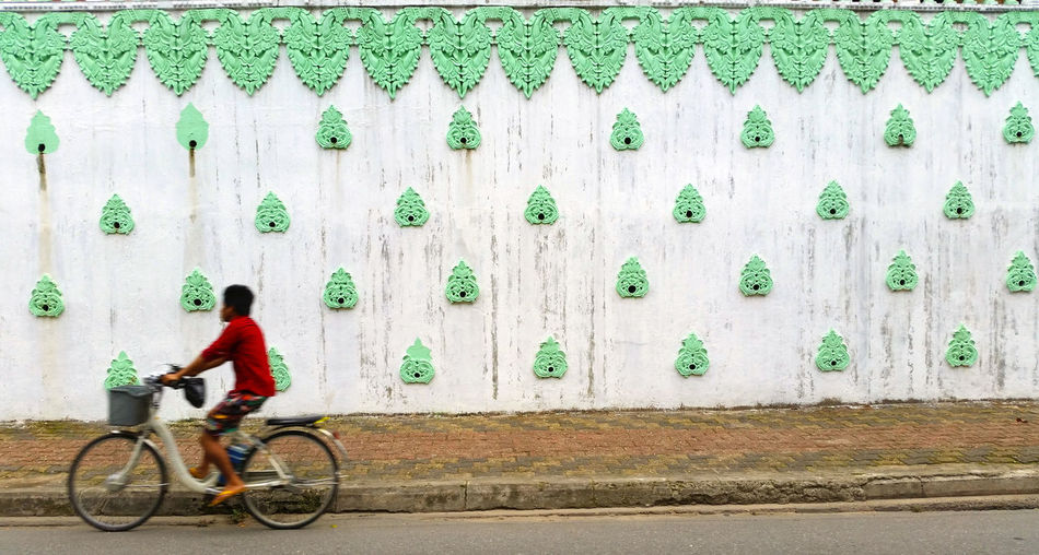 Boy Riding Bicycle On Street Against Carving On Wall