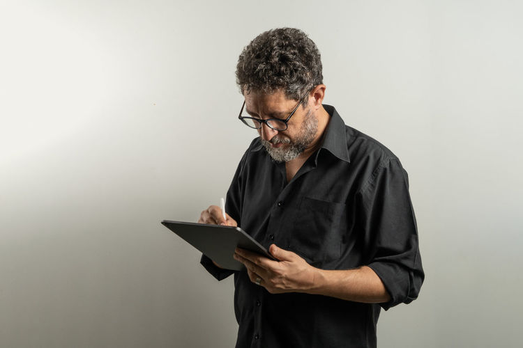 Man using digital tablet while standing against gray background