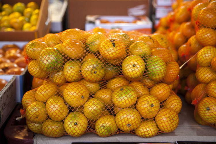 Close-up of tangerines in nets for sale at market stall