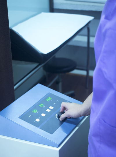 Close-up midsection of doctor adjusting medical equipment in hospital