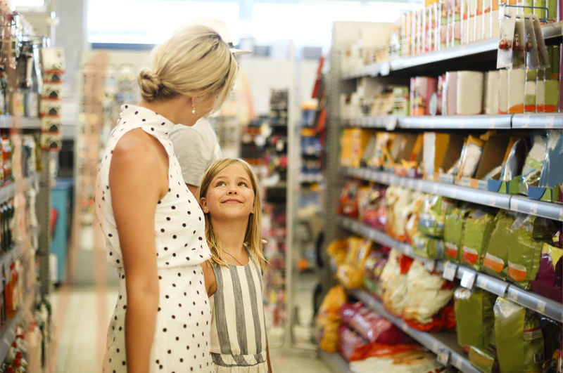 Side view of mother standing with daughter at supermarket