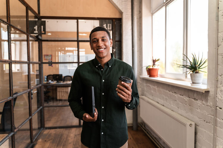 Portrait of smiling young man standing by window