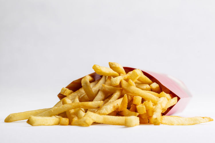 Close-up of fries with yellow noodles on white background
