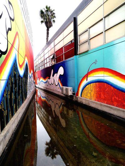 Graffiti on bridge over canal against sky