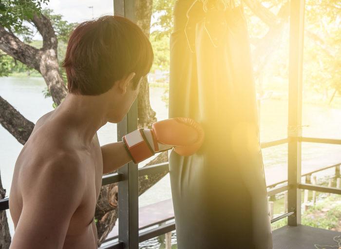 Man practicing boxing on punching bag