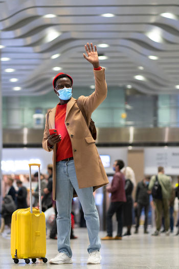 Full length of man wearing mask standing with hand raised at airport