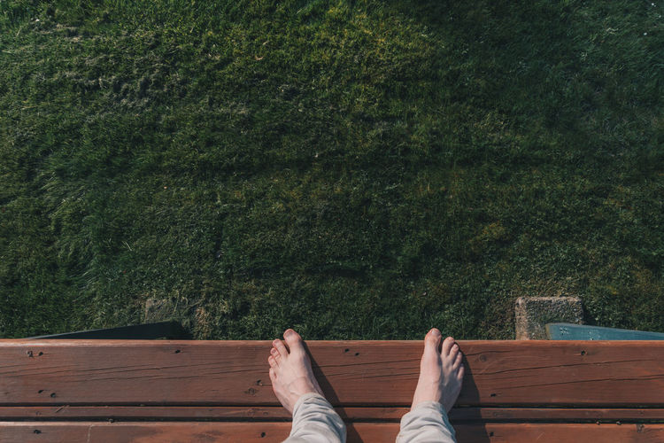 Mans feet over grass Adult Barefoot Day Deck Grass Human Body Part Human Foot Human Leg Low Section Nature One Person Outdoors Patio People Real People Relaxation Wood - Material Wooden Deck