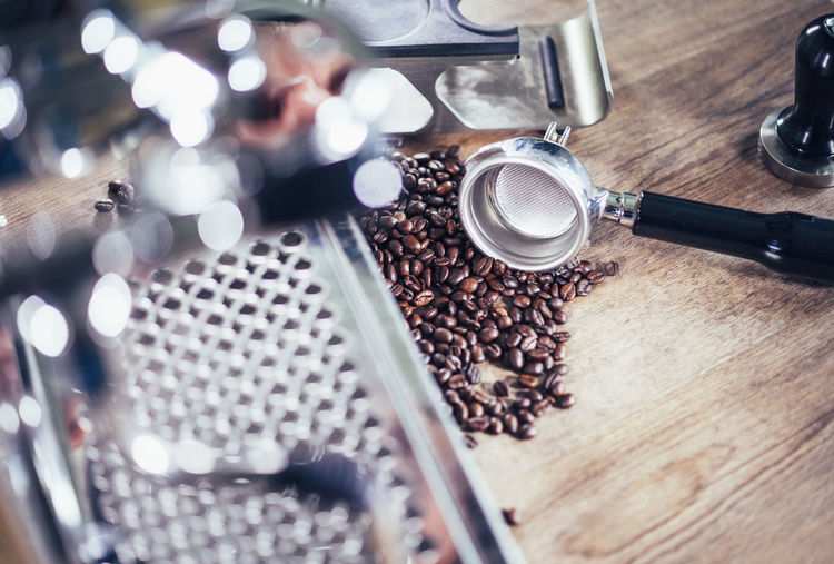 Close-up of machinery with coffee beans on table