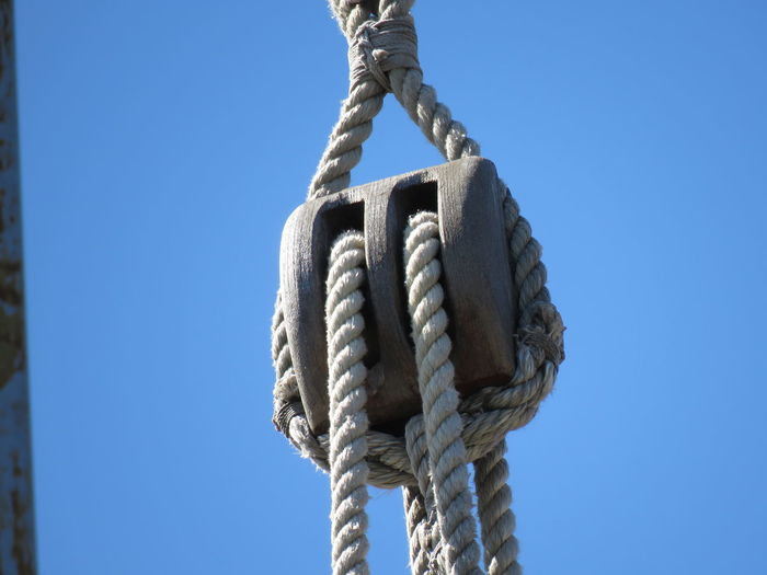 Close-up of rope tied up against blue sky