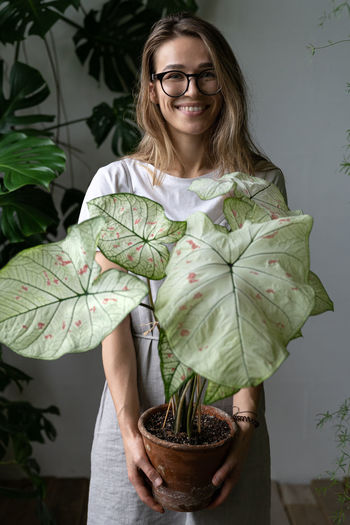 Portrait of smiling woman standing with potted plant