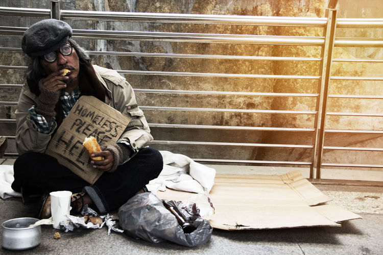 Homeless Man Holding Sign While Sitting On Footpath