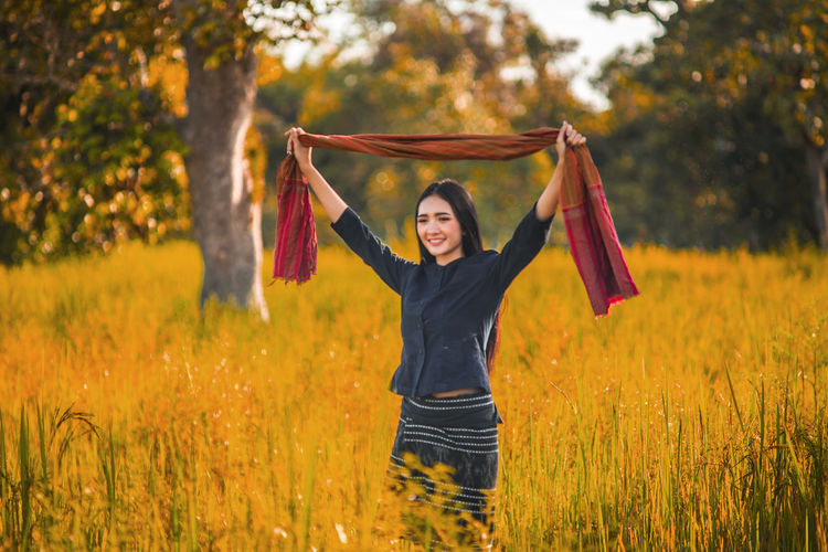 Happy young woman holding shawl while standing amidst grassy field