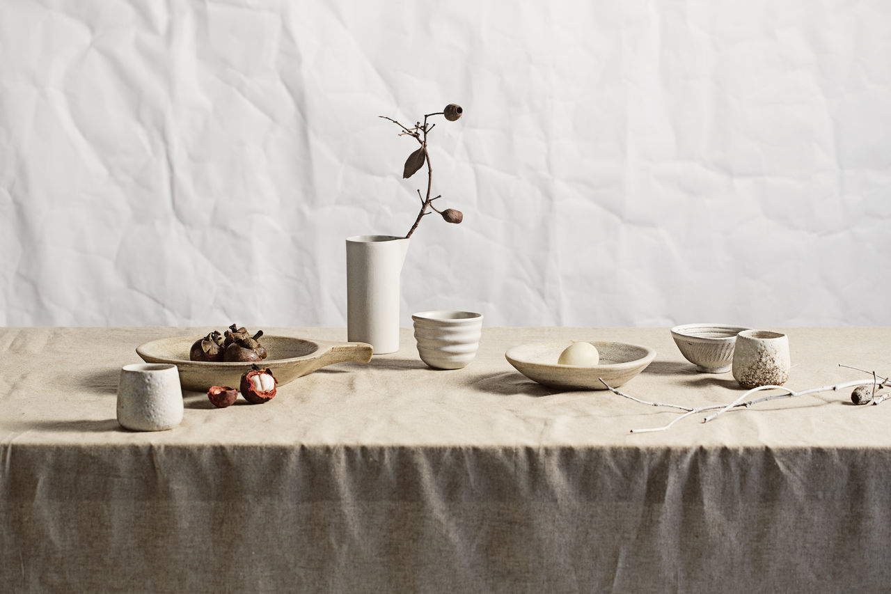 Food in bowls on table against curtain