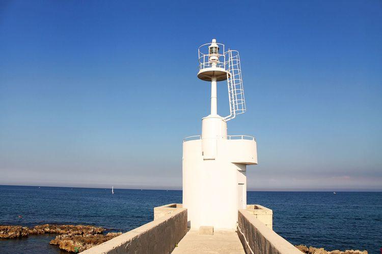 Lighthouse By Sea Against Clear Blue Sky