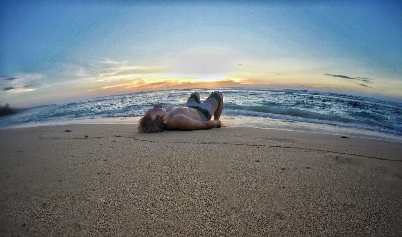 MAN LYING ON BEACH AGAINST SKY DURING SUNSET