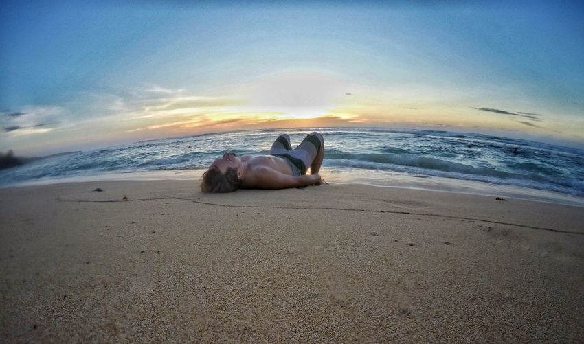 Man lying down on sand at beach against sky during sunset