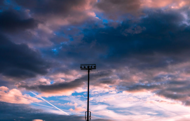 Low angle view of floodlight against clouds