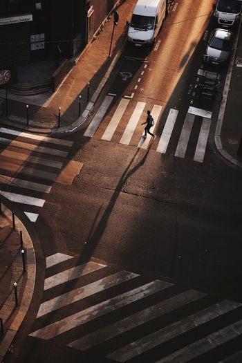 High Angle View Of Silhouette Man Crossing Street In City