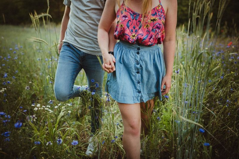 Midsection of man and woman holding hands while walking on grass