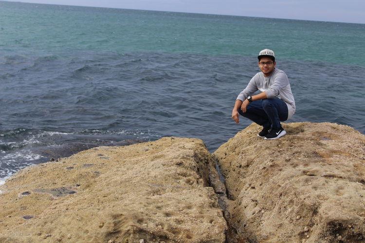 Full Length Portrait Of Man Crouching On Rock At Beach