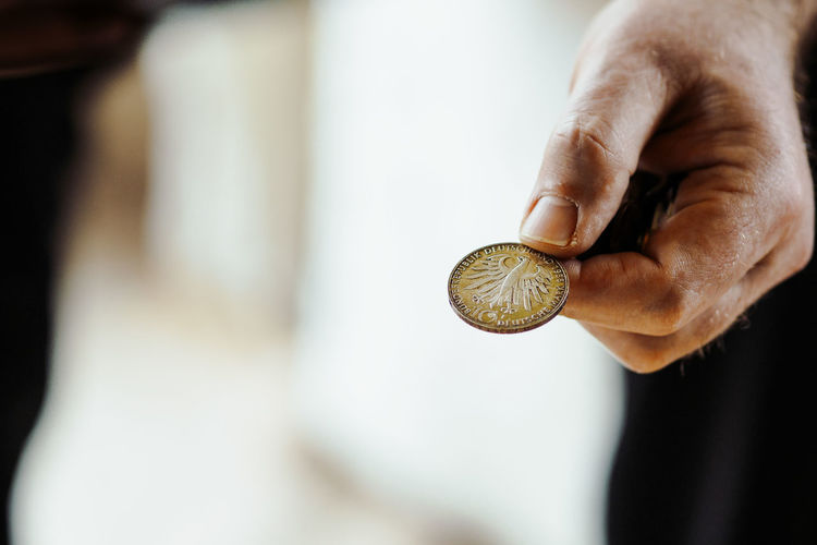 Close-Up Of Hand Holding Coin
