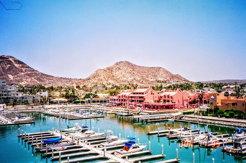 Getty Premium Premium Collection Mountain Architecture Water Moored Building Exterior Nautical Vessel Harbor No People Built Structure Travel Destinations Tranquility Outdoors Waterfront Mountain Range Day Scenics Clear Sky Yacht Sea 1995 Premium Collection Selected For Premium Yacht Club Marina Cabo San Lucas